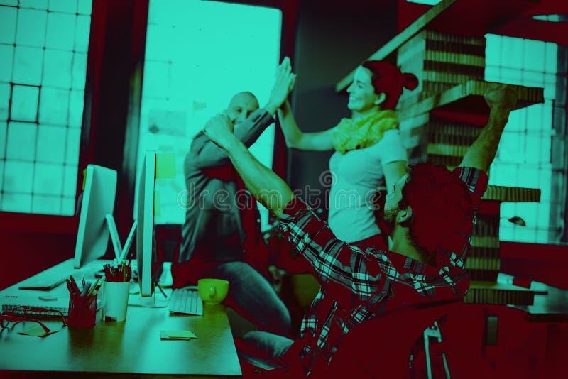 Hombres de negocios que animan en el escritorio del ordenador imagen de archivo