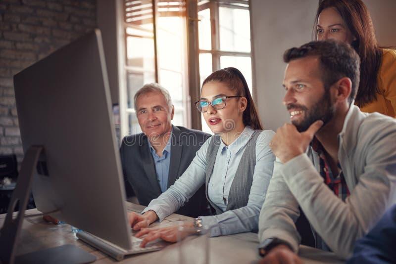 Hombres de negocios que animan en el ordenador imagenes de archivo