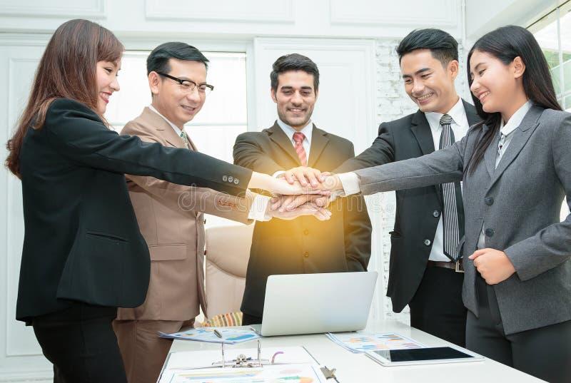 hombres de negocios que apilan las manos en sala de reunión imagen de archivo