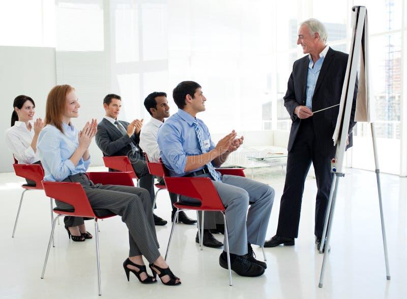 Hombres de negocios que aplauden en una conferencia foto de archivo