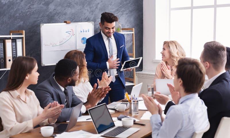 Hombres de negocios que aplauden para el colega después de la presentación imágenes de archivo libres de regalías