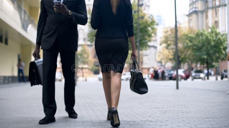 Hombres de negocios que caminan en la calle, comprobando el correo en smartphone, forma de vida ocupada fotos de archivo libres de regalías