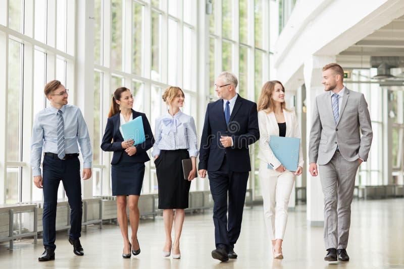 Hombres de negocios que caminan a lo largo del edificio de oficinas fotografía de archivo