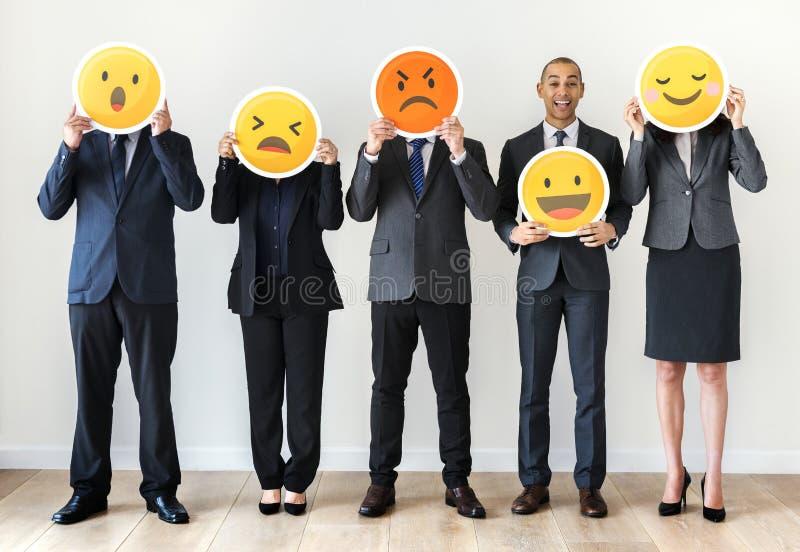 Hombres de negocios que colocan y que llevan a cabo iconos del emoji fotografía de archivo libre de regalías