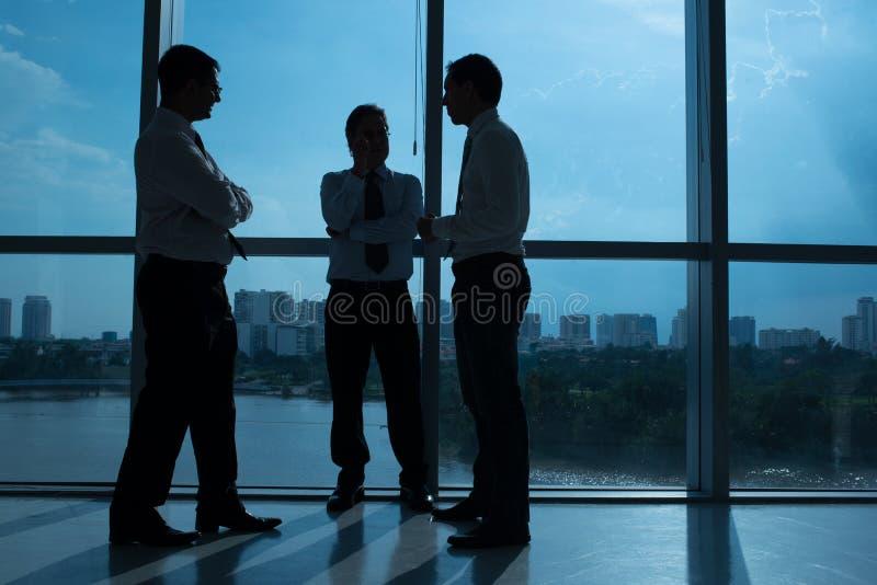 Hombres de negocios que comunican foto de archivo