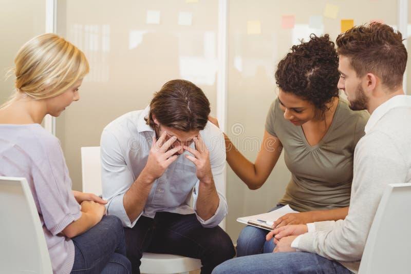 Hombres de negocios que consuelan al hombre de negocios que sufre de dolor de cabeza imagenes de archivo