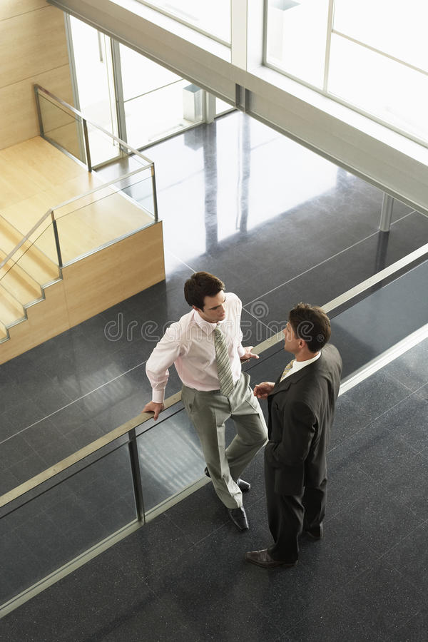 Hombres de negocios que conversan cercando con barandilla en oficina imagen de archivo libre de regalías