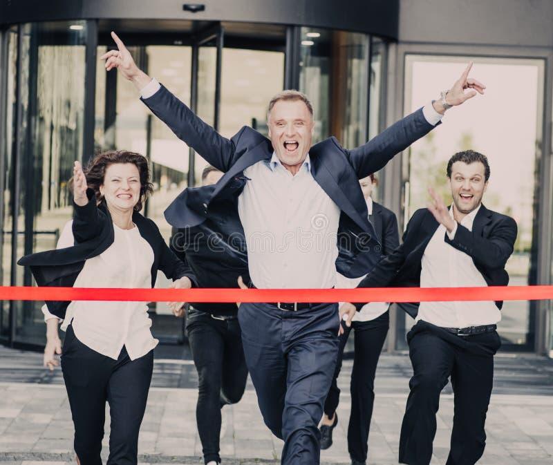 Hombres de negocios que cruzan la meta foto de archivo