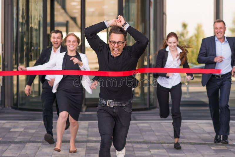 Hombres de negocios que cruzan la meta roja fotografía de archivo libre de regalías