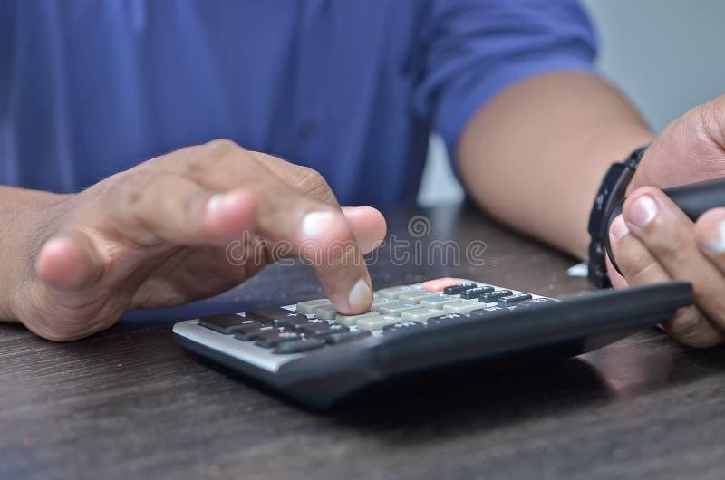 Hombres de negocios que cuentan en la calculadora que se sienta en la tabla Ci?rrese encima de la vista de manos y de efectos de  imagenes de archivo