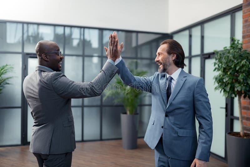 Hombres de negocios que dan arriba cinco después de la negociación acertada imagen de archivo