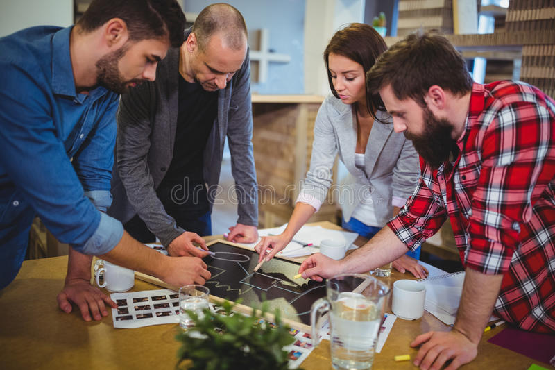Hombres de negocios que dibujan en la pizarra durante la reunión fotografía de archivo