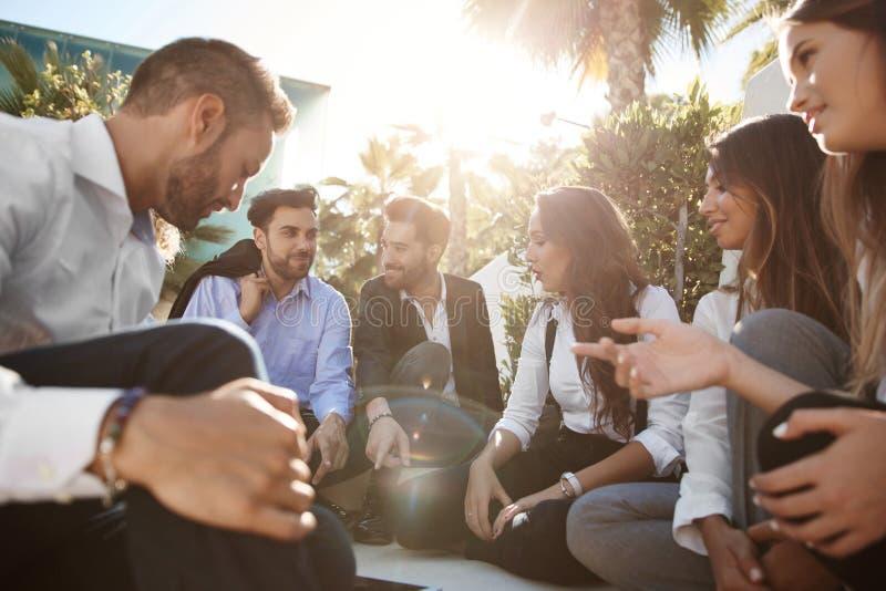 Hombres de negocios que discuten con los compañeros de trabajo afuera foto de archivo