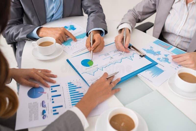 Hombres de negocios que discuten datos financieros imagenes de archivo