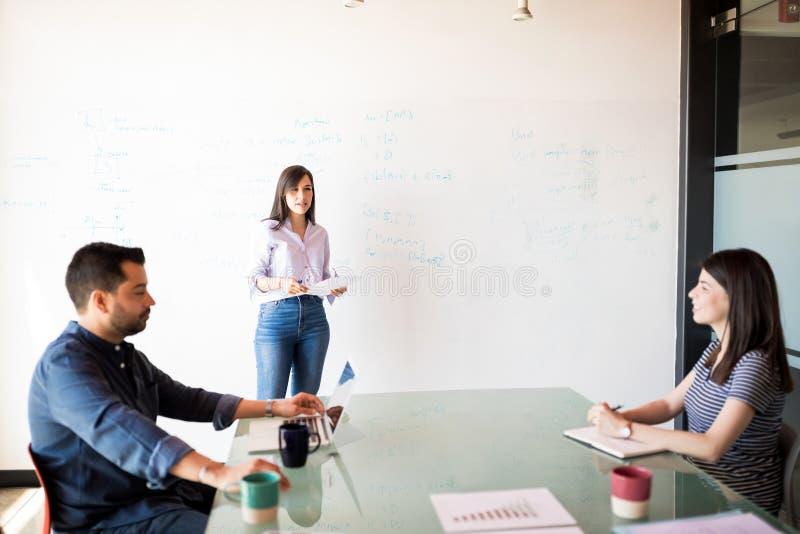 Hombres de negocios que discuten durante la presentación foto de archivo