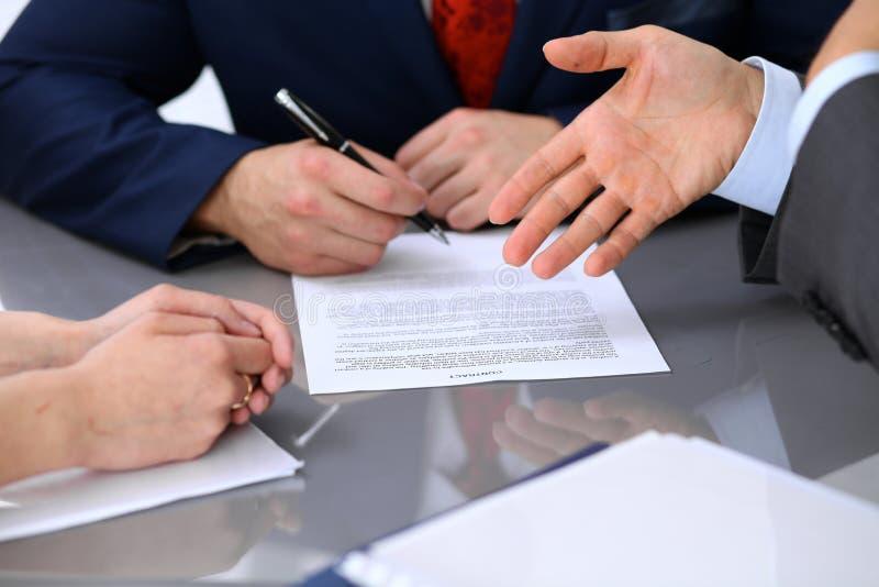Hombres de negocios que discuten el contrato Ciérrese para arriba de la mano masculina que señala al papel imagenes de archivo