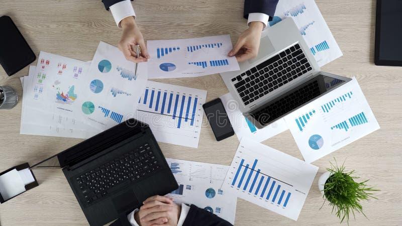 Hombres de negocios que discuten el diagrama de la renta de la compañía, estrategia de planificación junto fotografía de archivo