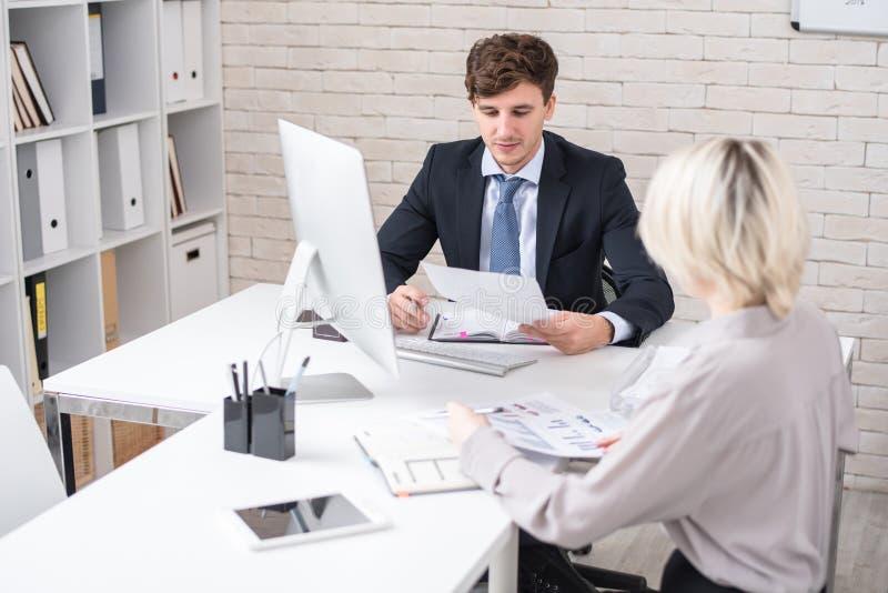 Hombres de negocios que discuten estadísticas durante la reunión en oficina imagen de archivo libre de regalías