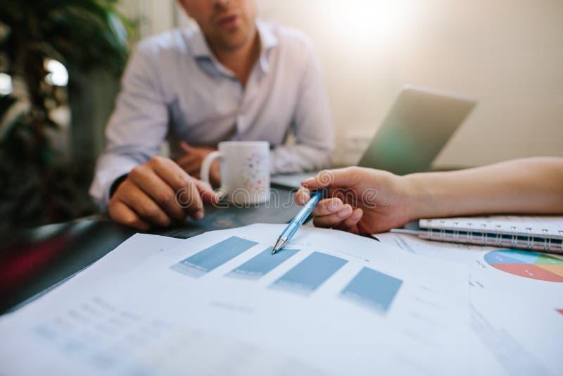 Hombres de negocios que discuten estadísticas financieras en oficina imagenes de archivo