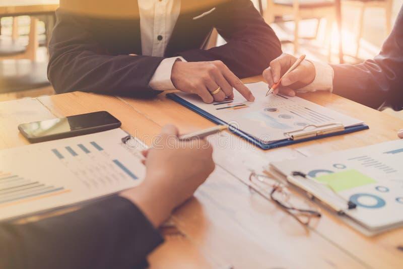 Hombres de negocios que discuten informes financieros en la reuni?n junta directiva el proyecto del planeamiento, considerando of fotos de archivo libres de regalías