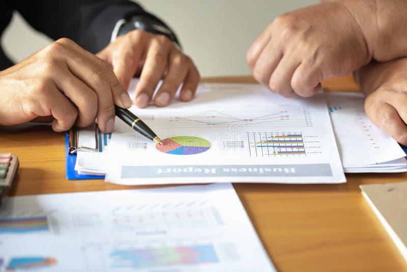 Hombres de negocios que discuten las cartas y los gráficos que muestran los resultados de su trabajo en equipo acertado fotos de archivo