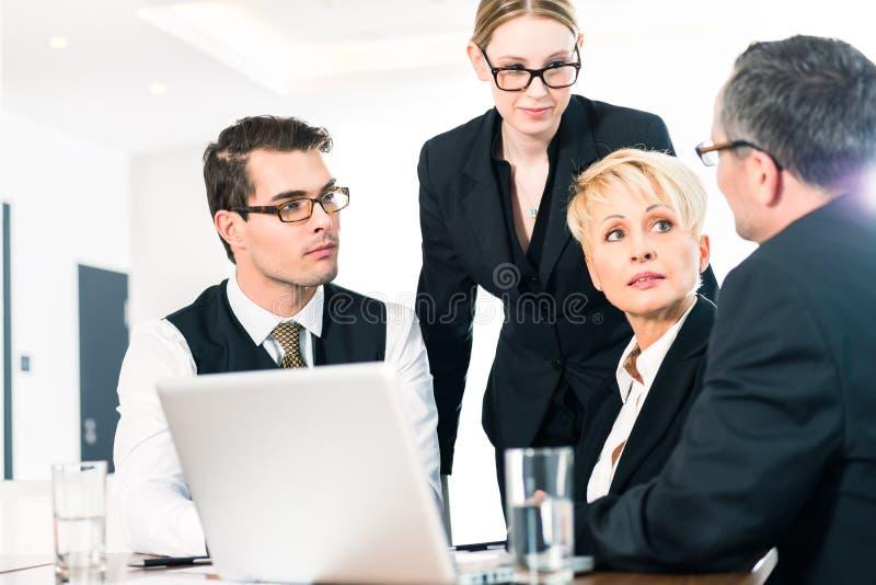 Hombres de negocios que discuten plan en oficina imagenes de archivo