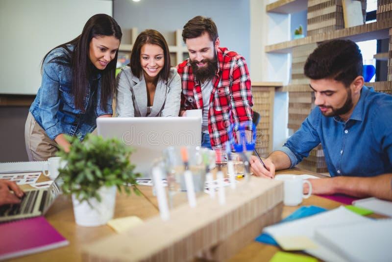 Hombres de negocios que discuten sobre el ordenador portátil en el escritorio imagen de archivo