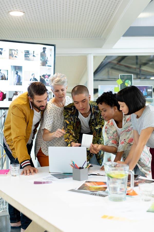 Hombres de negocios que discuten sobre el ordenador portátil en la sala de conferencias fotografía de archivo libre de regalías