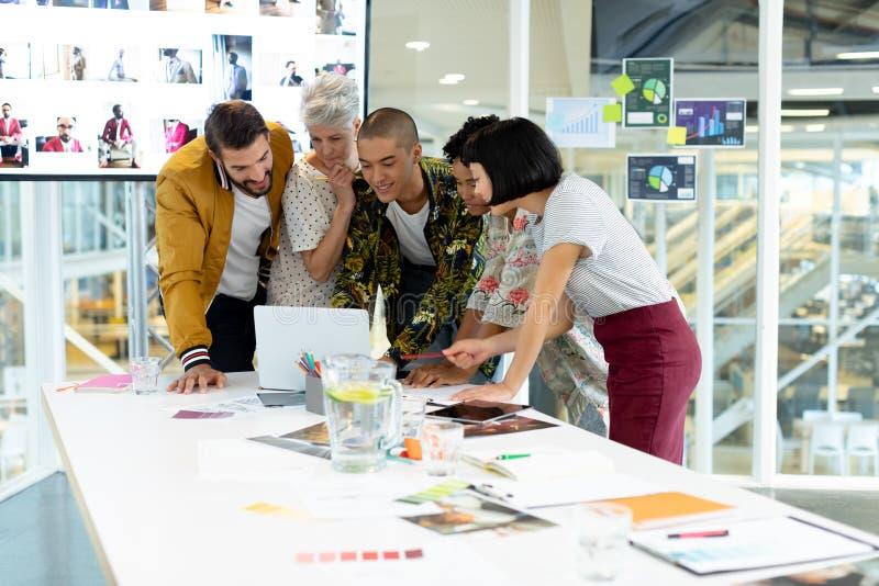Hombres de negocios que discuten sobre el ordenador portátil en la sala de conferencias fotografía de archivo