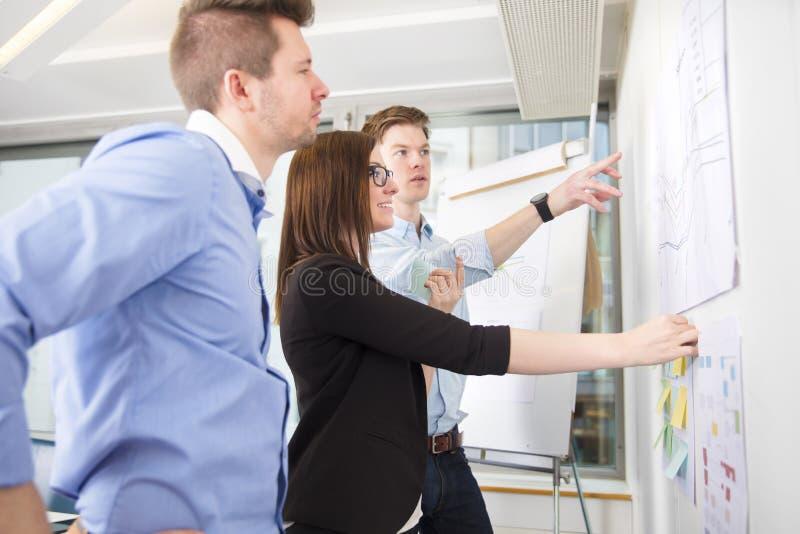 Hombres de negocios que discuten sobre la línea gráfico pegado en la pared fotografía de archivo