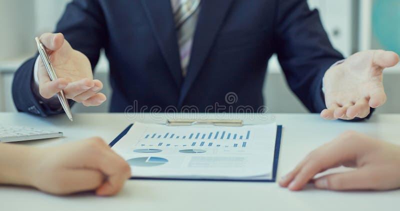 Hombres de negocios que discuten y que analizan datos del gráfico en la reunión Apenas entrega la tabla fotografía de archivo libre de regalías