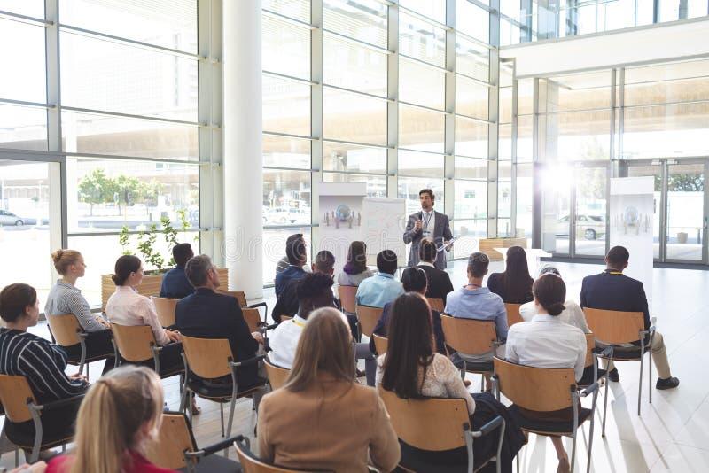 Hombres de negocios que escuchan el hombre de negocios y que hacen preguntas en la conferencia fotos de archivo