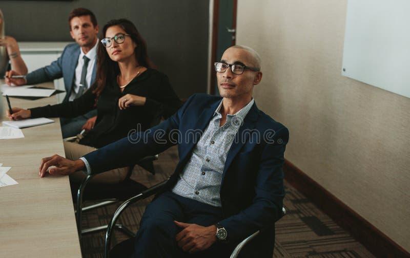 Hombres de negocios que escuchan el informe corporativo imagenes de archivo