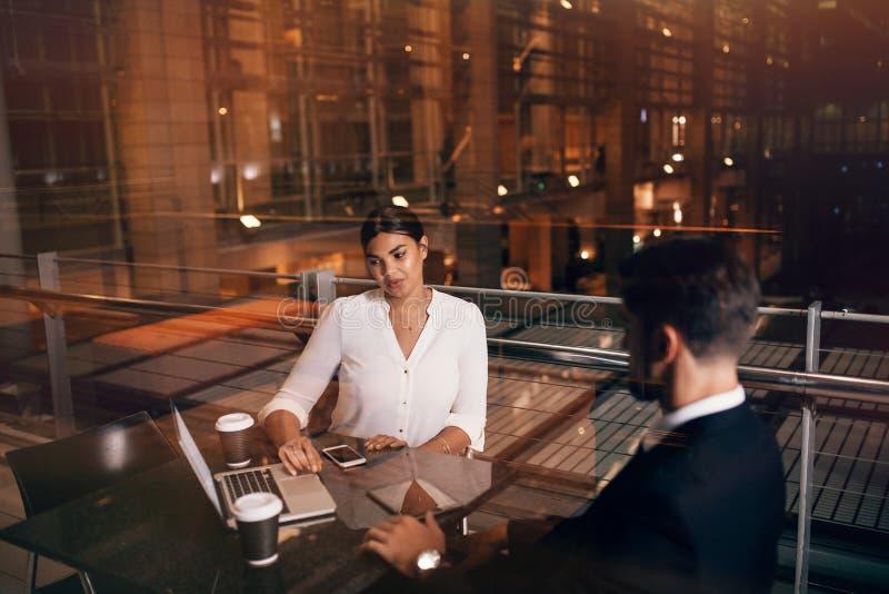 Hombres de negocios que esperan en el salón del aeropuerto con el ordenador portátil fotos de archivo