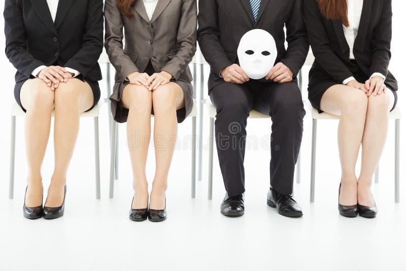 Hombres de negocios que esperan entrevista de trabajo con una máscara extraña fotografía de archivo