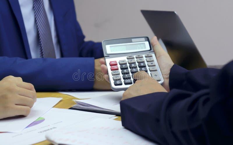 Hombres de negocios que están presionando las calculadoras y están comunicando con los amigos para analizar la información del tr imagen de archivo libre de regalías