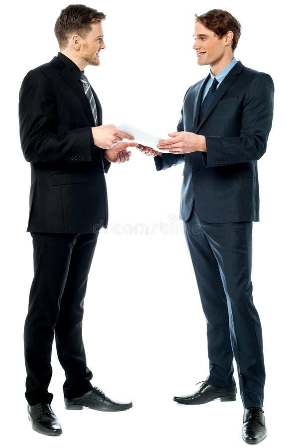 Hombres de negocios que evalúan documentos del trato foto de archivo libre de regalías