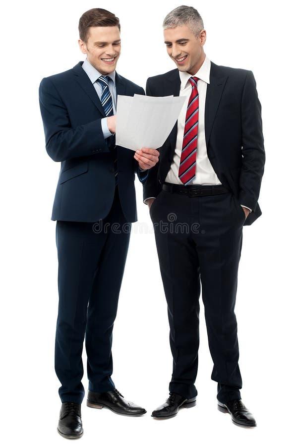 Hombres de negocios que evalúan documentos del trato fotos de archivo