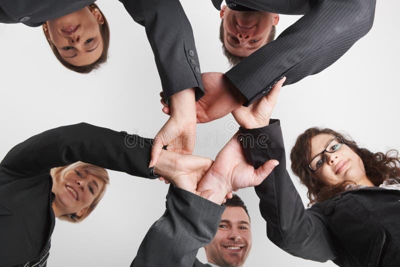 Hombres de negocios que forman el anillo del ángulo bajo de las manos imagen de archivo