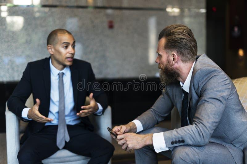 Hombres de negocios que hablan al colega serio del intercambio de ideas imágenes de archivo libres de regalías