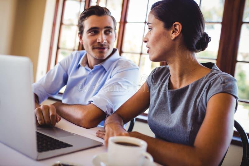 Hombres de negocios que hablan con uno a en restaurante imagen de archivo