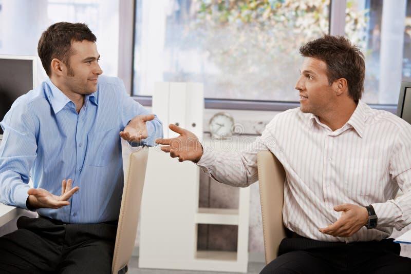 Hombres de negocios que hablan en oficina fotografía de archivo libre de regalías