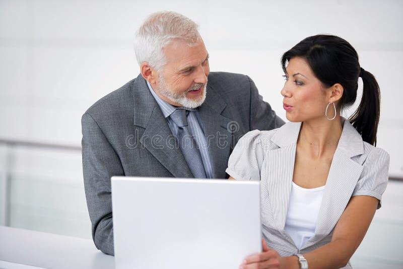 Hombres de negocios que hablan en un pasillo imagenes de archivo
