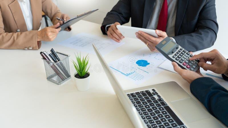 Hombres de negocios que hablan la discusión con el planeamiento del compañero de trabajo que analiza cartas y gráficos financiero fotos de archivo
