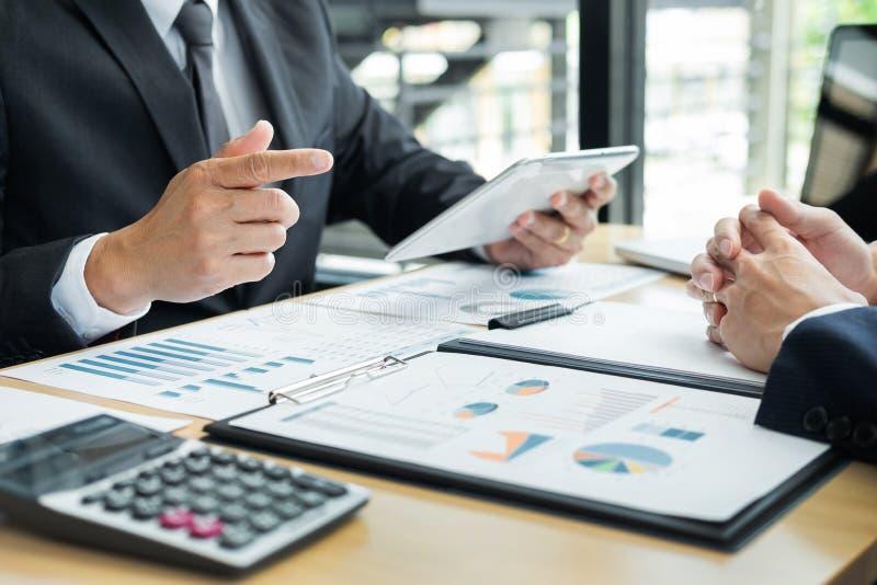 Hombres de negocios que hablan la discusión con el planeamiento del compañero de trabajo que analiza cartas y gráficos financiero imagenes de archivo