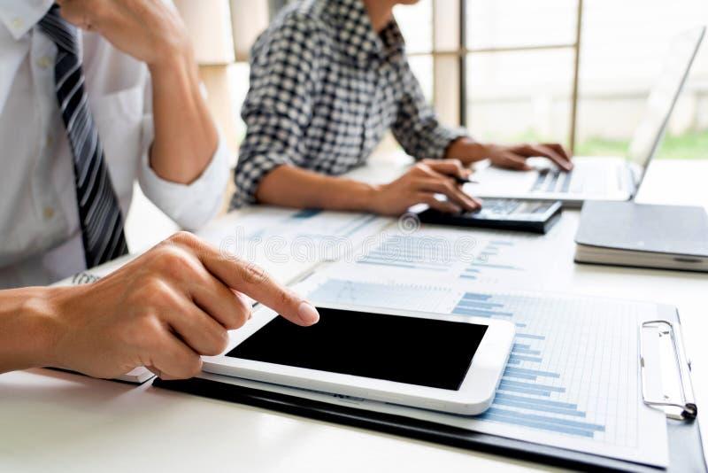 Hombres de negocios que hablan la discusión con el planeamiento del compañero de trabajo que analiza cartas y gráficos financiero imagen de archivo