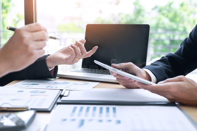 Hombres de negocios que hablan la discusión con el planeamiento del compañero de trabajo que analiza cartas y gráficos financiero fotografía de archivo