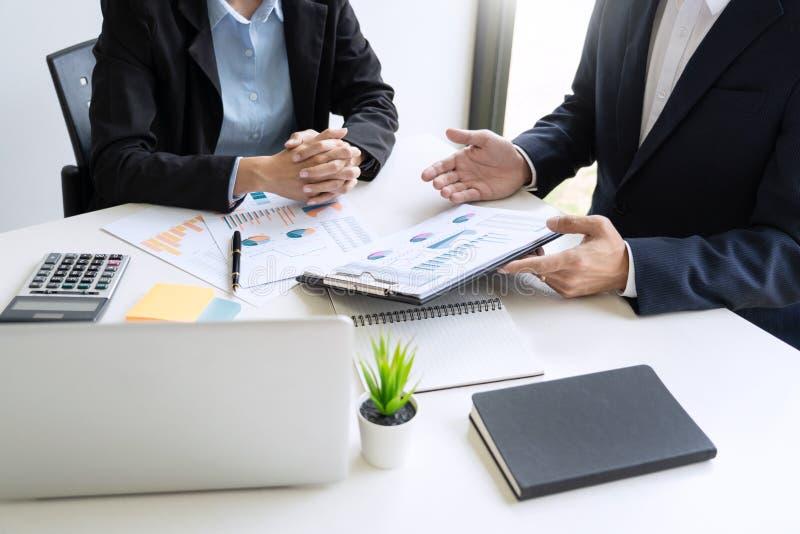 Hombres de negocios que hablan la discusión con el planeamiento del compañero de trabajo que analiza cartas y gráficos financiero imagen de archivo libre de regalías