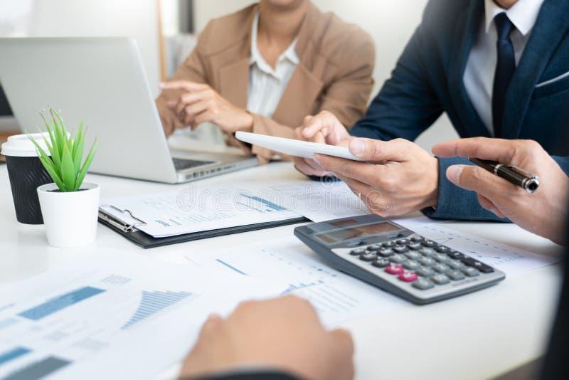 Hombres de negocios que hablan la discusión con el planeamiento del compañero de trabajo que analiza cartas y gráficos financiero foto de archivo