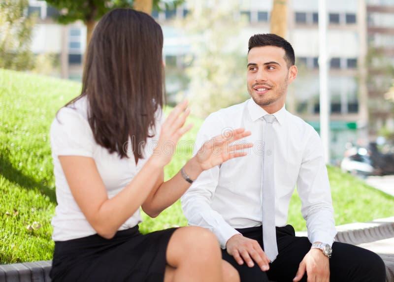 Hombres de negocios que hablan mientras que se sienta al aire libre foto de archivo